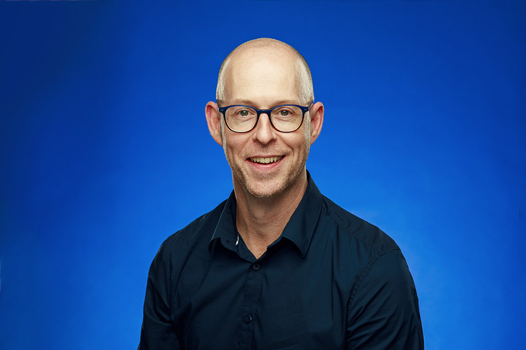 middle aged bald businessman wearing glasses smiling navy blue shirt electric blue background