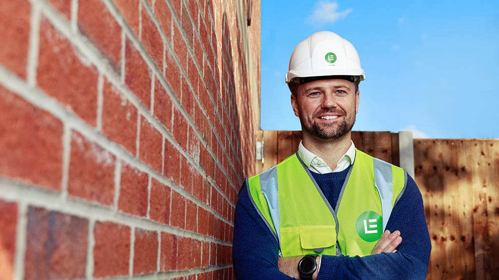 Construction worker in PPE and hard hat arms folded smiling blue sky behind red brick wall to side