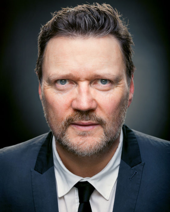 actor headshot portrait featuring Ian Puleston-Davies wearing teddy body jacket, tie and hairstyle