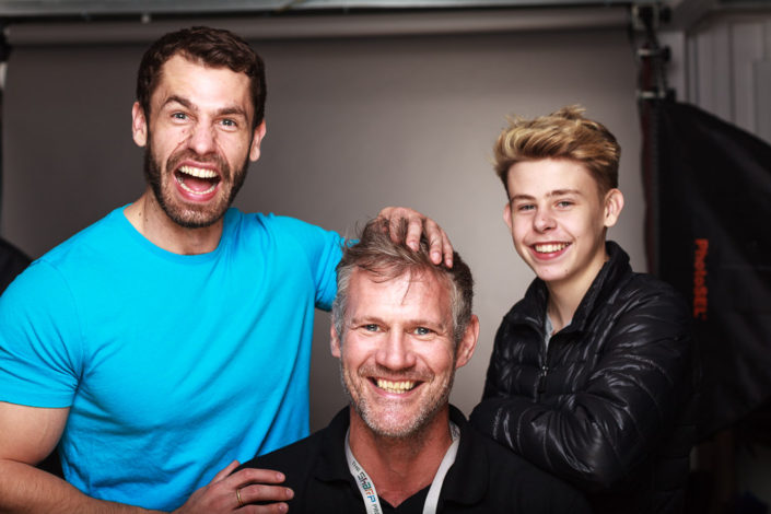 Behind scenes group shot features actor Kelvin Fletcher, Brayden Fletcher and Colin Boulter in the studio after a shoot. photographed against a black background with studio light in shot