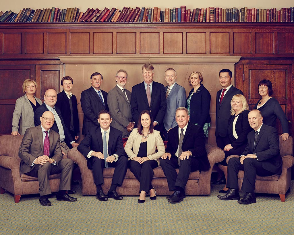 Large group of middle aged business people taken in an old wood panelled room with chesterfield settee and book shelf above