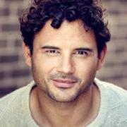 actor headshot featuring Ryan Thomas taken outside against brown brick wall
