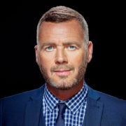 portrait of a gary barlow look a like wearing blue jacket and shirt on black background