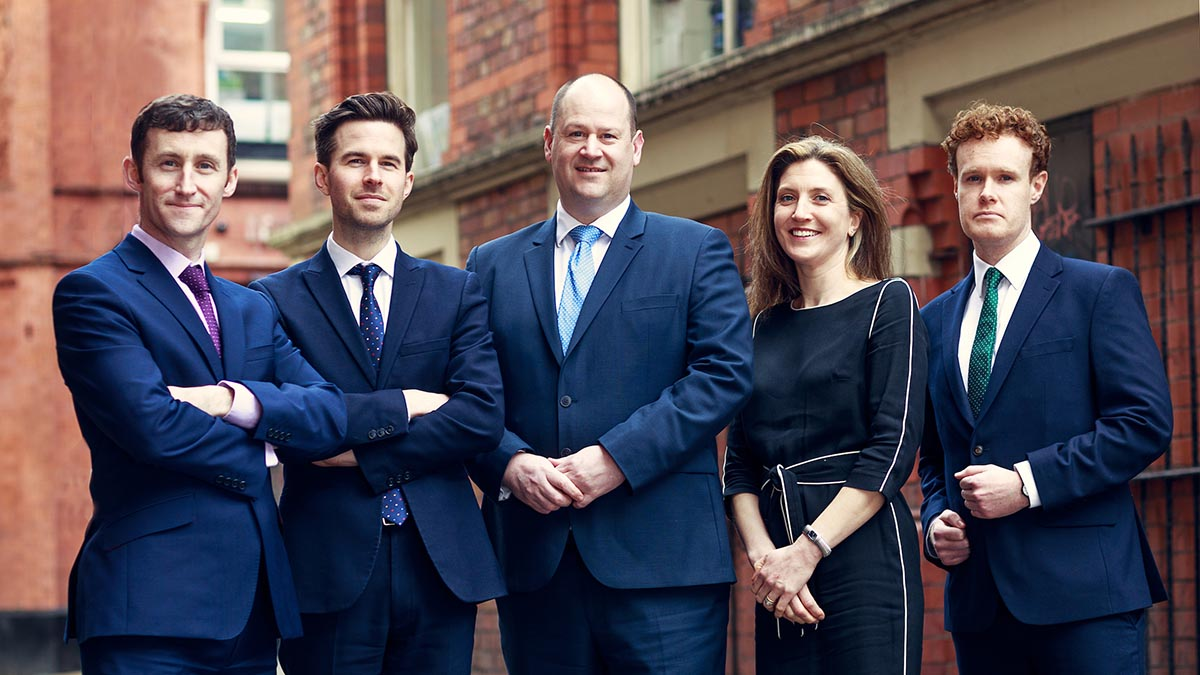 5 business people wearing suits stood in line with red brick buildings behind them