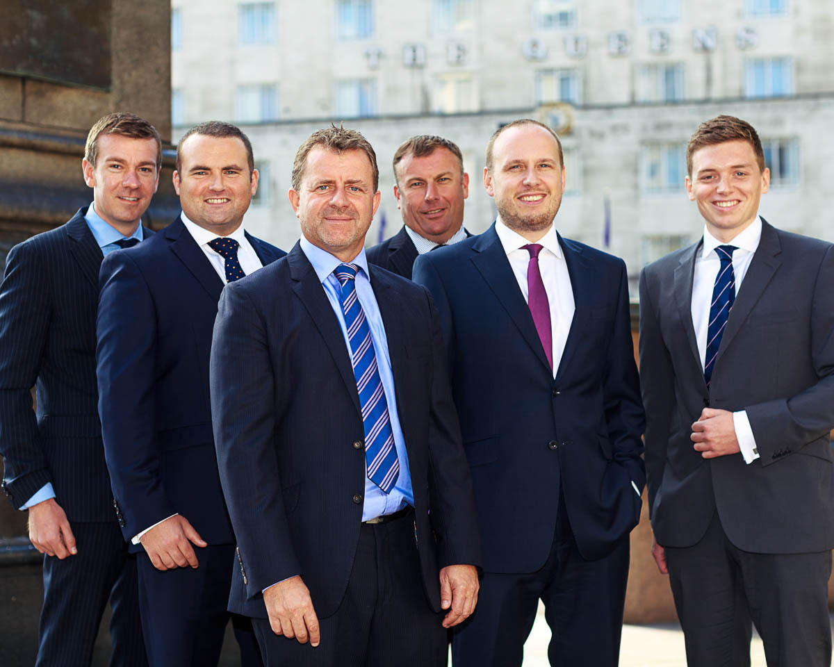 six businessmen blue suits standing side by side office background
