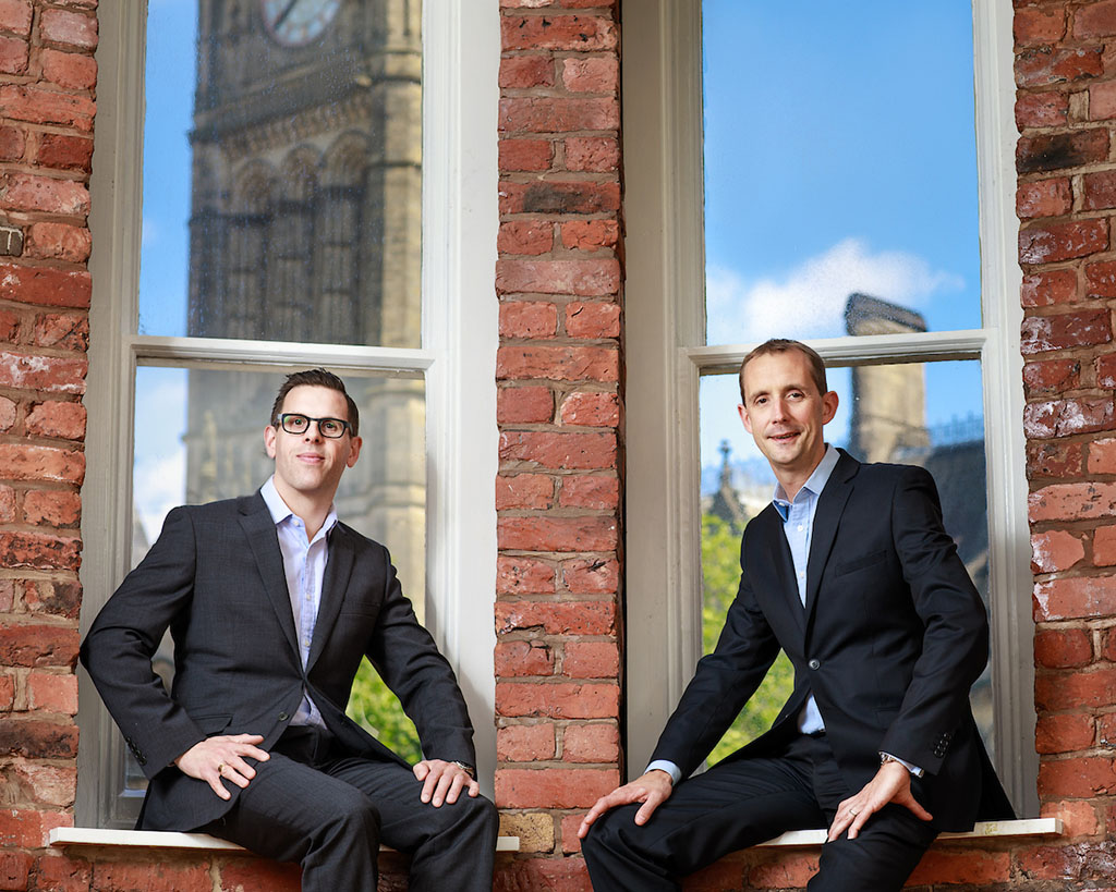 2 business man sat on window sill with big windows behind them showing Manchester town hall and blue sky