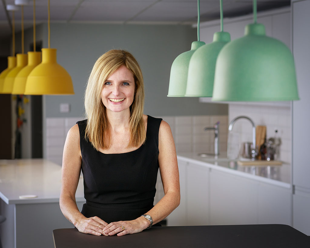 middle aged business lady in modern kitchen with modern lamps seen in shot
