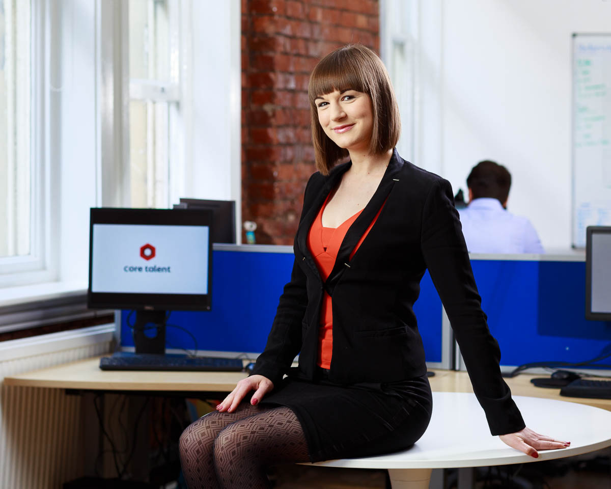 young business lady sat on desk creative office space with bare bricks and big windows in background