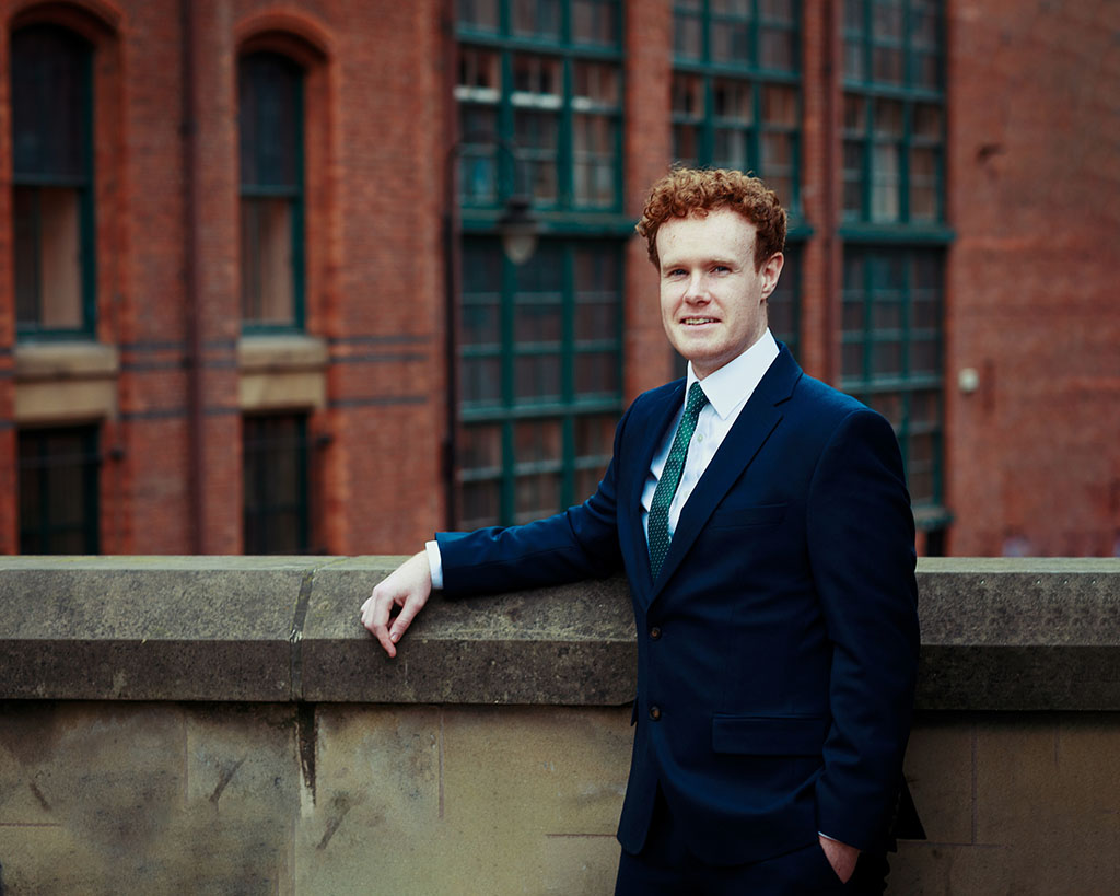 young business man in suit with red hair back suit green tie and red brick building behind them