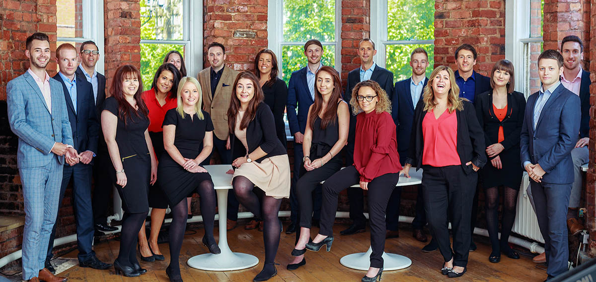 Large corporate group shot featuring young recruitment consultants red brick wall behind them